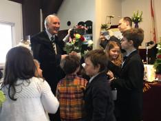 gyermekek rózsával köszöntik a püspököt
