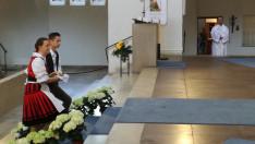 A Misszió népviseletbe öltözött tagjai viszik a kenyeret az oltárra