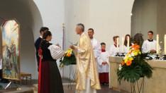 A Misszió népviseletbe öltözött tagjai viszik a bort az oltárra
