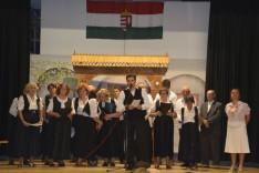 Szennyessy László, a MagyarHáz Alapítvány elnöke megnyitja a rendezvényt, háttérben a Golarits kórus