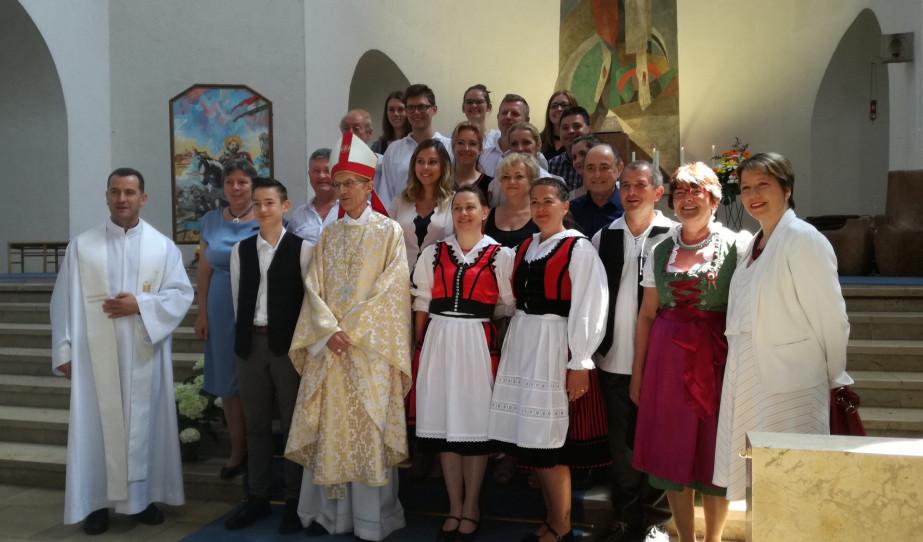 Majnek Antal segédpüspök (középen) az augsburgi Magyar Misszió plébánosával (balra), Spiller Krisztina közösségi diplomatával (jobbra) és a Misszió kórusával