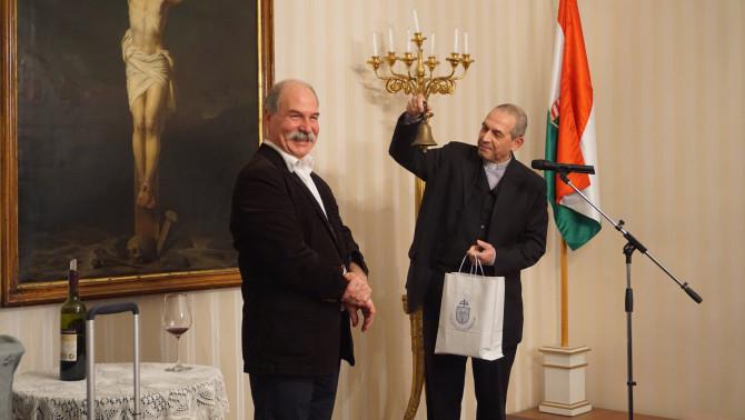 Varga János atya átadja az előadóművésznek ajándékként a kis harangot